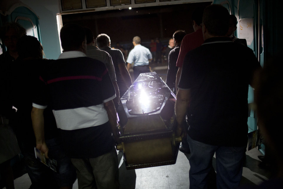 Photo - Relatives and friends carry the coffin of a victim out of a gymnasium where bodies where brought for identification in Santa Maria city, Rio Grande do Sul state, Brazil, Sunday, Jan. 27, 2013.  A fast-moving fire roared through the crowded, windowless Kiss nightclub in southern Brazil early Sunday, within seconds filling the space with flames and a thick, toxic smoke that killed more than 230 panicked partygoers who gasped for breath and fought in a stampede to escape.(AP Photo/Felipe Dana)