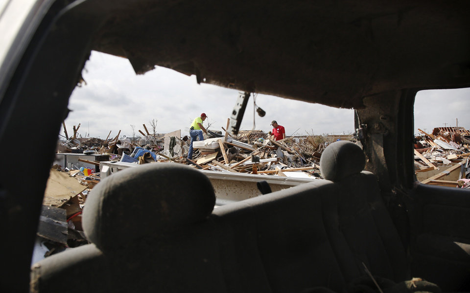 Photo - Two men from the First Baptist Church of Moore are seen through the broken out back window of a pickup truck. Volunteers from various parts of the country joined Oklahomans in assisting residents on Saturday,  May 25, 2013, doing whatever was needed to remove debris and salvage items from this neighborhood east of Santa Fe, north of SW 19 Street.  An EF5 tornado leveled many neighborhoods in Moore and southwest Oklahoma City last Monday.   Photo  by Jim Beckel, The Oklahoman.