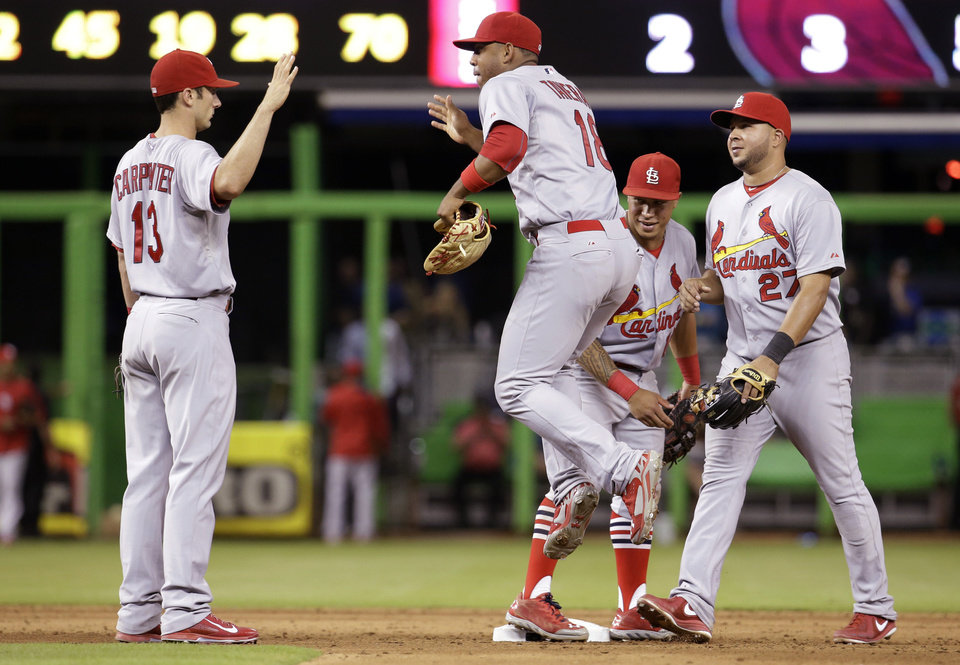Photo - St. Louis Cardinals third baseman Matt Carpenter (13), right fielder Oscar Taveras (18), second baseman Kolten Wong, second from right, and shortstop Jhonny Peralta (27) celebrate after the defeating the Miami Marlins 5-2 during a baseball game, Wednesday, Aug.13, 2014, in Miami. (AP Photo/Lynne Sladky)