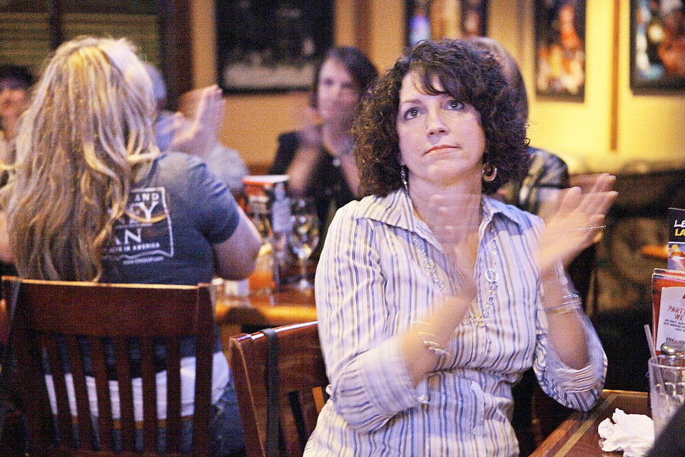 Marcia Jolly claps Monday as she watches the debate with other state Republicans at the Fox and Hound in Oklahoma City.  Photo By  David McDaniel, The Oklahoman
