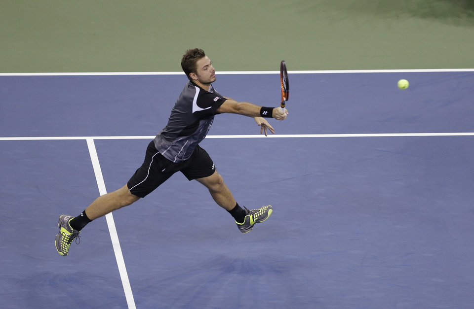 Photo - Stan Wawrinka, of Switzerland, returns a shot to Thomaz Bellucci, of Brazil, during the second round of the U.S. Open tennis tournament Wednesday, Aug. 27, 2014, in New York. (AP Photo/Darron Cummings)