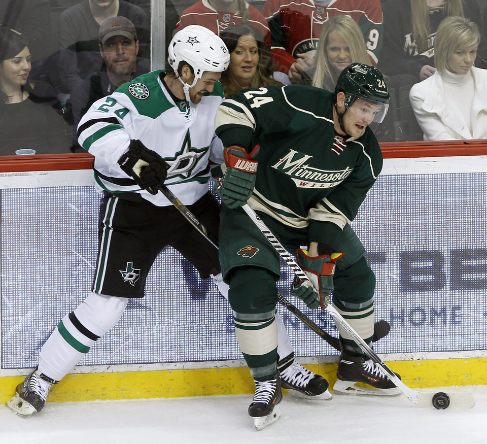 Photo - Minnesota Wild left wing Matt Cooke, right, controls the puck in front of Dallas Stars defenseman Jordie Benn, left, during the first period of an NHL hockey game in St. Paul, Minn., Saturday, Jan. 18, 2014.  (AP Photo/Ann Heisenfelt)