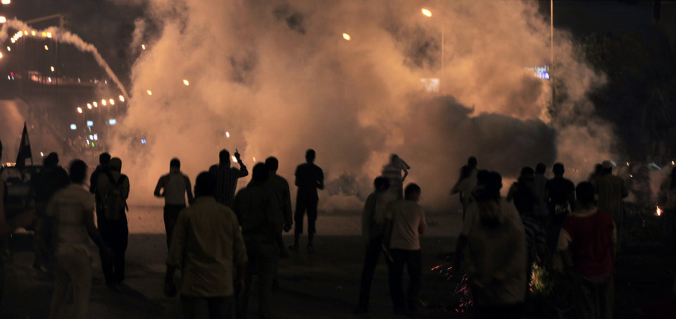 Photo - Supporters of Egypt's ousted President Mohammed Morsi clash with riot police at Nasr City, where protesters have installed their camp and hold their daily rally, in Cairo, Friday, July 26, 2013. Prosecutors opened an investigation of ousted President Mohammed Morsi on charges including murder and conspiracy with the Palestinian militant group Hamas, fueling tensions amid a showdown in the streets between tens of thousands of backers of the military and supporters calling for the Islamist leader's reinstatement. (AP Photo/Khalil Hamra)