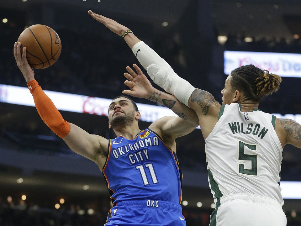 Photo - Oklahoma City Thunder's Abdel Nader shoots against Milwaukee Bucks' D.J. Wilson during the first half of an NBA basketball game Wednesday, April 10, 2019, in Milwaukee. (AP Photo/Aaron Gash)