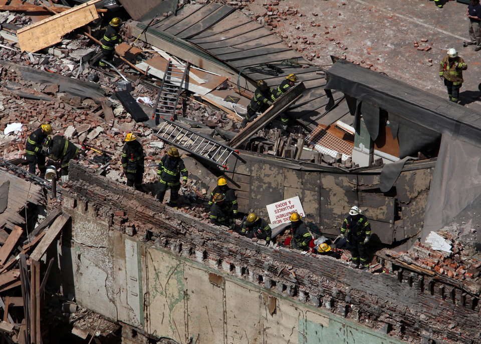Photo - Rescue personnel search the scene of a building collapse in downtown Philadelphia Wednesday June 5, 2013.  A four-story building being demolished collapsed Wednesday on the edge of downtown, injuring 12 people and trapping two others, the fire commissioner said. Rescue crews were trying to extricate the two people who were trapped, city Fire Commissioner Lloyd Ayers said. The dozen people who were injured were taken to hospitals with minor injuries, he said. (AP Photo/Jacqueline Larma)