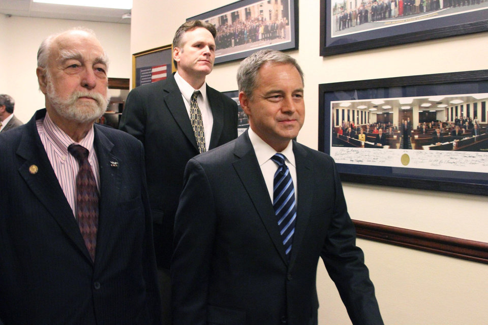 Photo - Alaska Gov. Sean Parnell, right, is led into the House chamber for his State of the State speech by Rep. Bob Lynn, R-Anchorage, left, and Sen. Mike Dunleavy, R-Wasilla, Wednesday, Jan. 22, 2014, in Juneau, Alaska. Parnell used the address to lay out plans to change Alaska's education system, including improving access to charter schools and boosting public school funding. (AP Photo/Mark Thiessen)