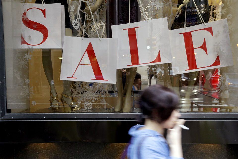 "Photo - In this Tuesday, Dec. 18, 2012, photo, a person passes a retail store with sale sign displayed in the window in Philadelphia. When it comes to big discounts, better late than never. This holiday shopping season, stores haven't been offering the same big discounts as they did in previous years as they tried to lure shoppers in with other incentives,but during the final days leading up to Christmas, shoppers will see more of those jaw-dropping ""70 percent off"" sale signs as stores try to salvage a season that so far has been disappointing.  (AP Photo/Matt Rourke)"