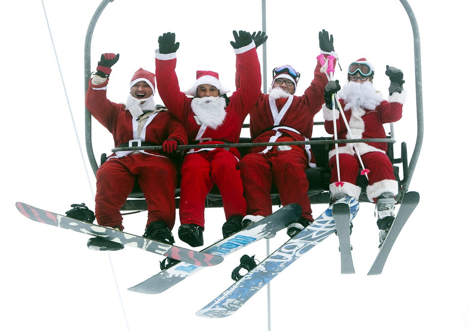Photo - A group of Santas ride a chairlift, Sunday, Dec. 2, 2012, at the Sunday River Ski Resort in Newry, Maine. More than 250 skiers and snowboarders participated in the annual Santa Sunday event to raise money to benefit the Bethel Rotary Club's Christmas for Children program.(AP Photo/Robert F. Bukaty)