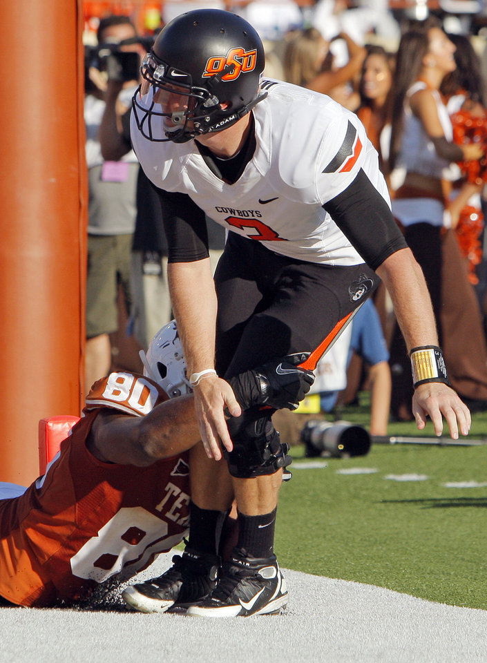 Photo - Oklahoma State's Brandon Weeden (3) is brought down by Texas' Alex Okafor (80) after Weeden stepped out of the back of the end zone for a safety in the fourth quarter during a college football game between the Oklahoma State University Cowboys (OSU) and the University of Texas Longhorns (UT) at Darrell K Royal-Texas Memorial Stadium in Austin, Texas, Saturday, Oct. 15, 2011. OSU won, 38-26. Photo by Nate Billings, The Oklahoman