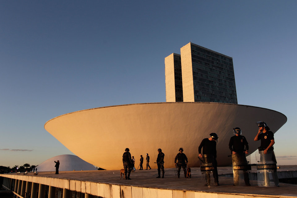 Photo - Police guard the building of Brazil's National Congress during a protest in Brasilia, Brazil, Thursday, June 20, 2013. President Dilma Rousseff called an emergency meeting of her top Cabinet members for Friday morning, more than a week after the protests began. Rousseff, who has a standoffish governing style, has been almost entirely absent from the public eye, making only one statement earlier in the week that peaceful protests are part of the democratic process. (AP Photo/Eraldo Peres)