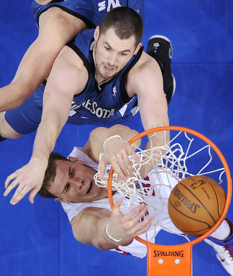 Photo - Los Angeles Clippers forward Blake Griffin, below, dunks as forward Minnesota Timberwolves' Kevin Love defends during the first half of an NBA basketball game, Wednesday, Jan. 19, 2011, in Los Angeles. (AP Photo/Mark J. Terrill)