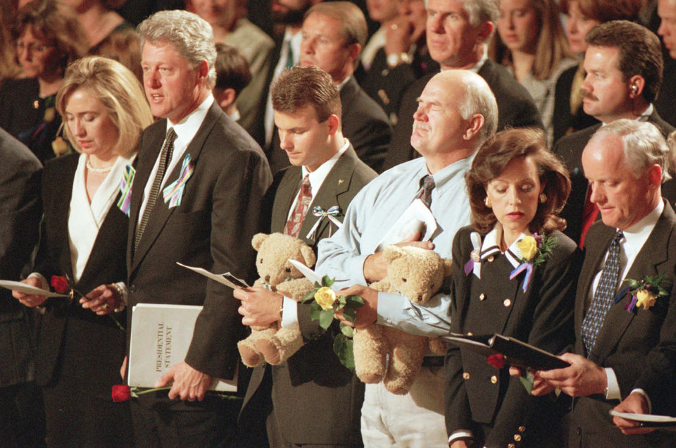 Photo - ALFRED P. MURRAH FEDERAL BUILDING, CAR, TRUCK, BOMB, EXPLOSION, BOMBING: Hillary and President Bill Clinton, Cathy and Gov. Frank Keating, Jason Smith and Dan McKinney, son and husband of Secret Service employee Linda McKinney who was killed in the Alfred Murrah Federal Building car bomb explosion singing Amazing Grace during memorial service.