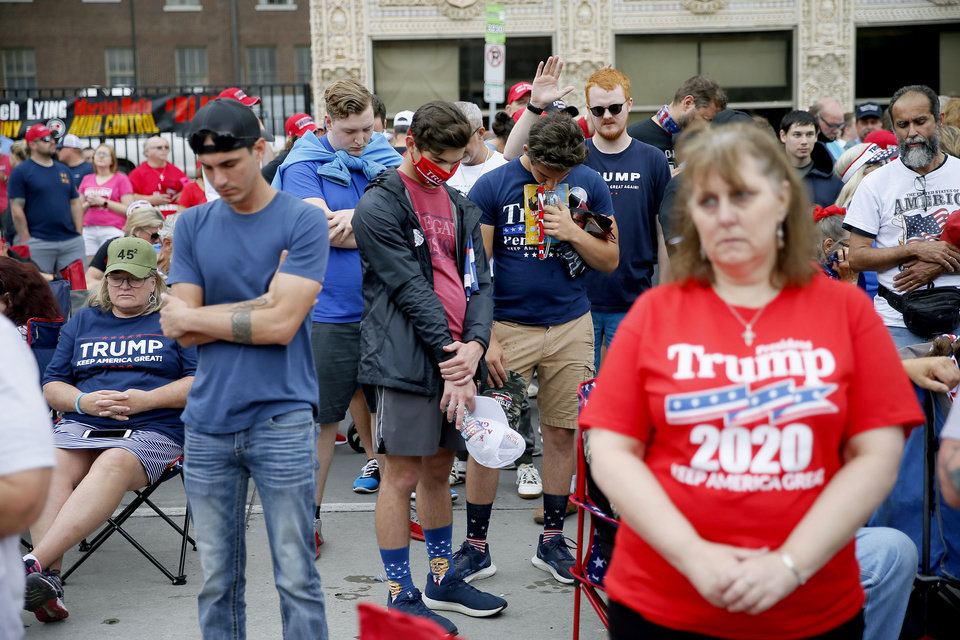 Photo - President Donald Trump supporters pray as they wait outside a security gate before a rally at the BOK Center in Tulsa, Okla., Saturday, June 20, 2020. [Bryan Terry/The Oklahoman]