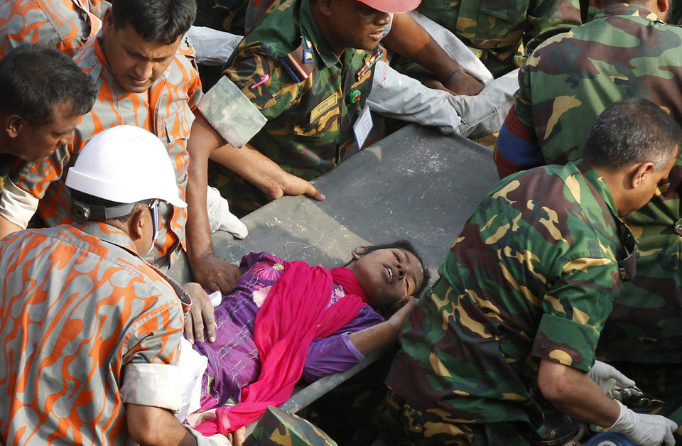 Photo - Rescuers carry a survivor pulled out from the rubble of a building that collapsed in Saver, near Dhaka, Bangladesh, Friday, May 10, 2013. Rescue workers in Bangladesh freed the woman buried for 17 days inside the wreckage of a garment factory building that collapsed, killing more than 1,000 people. Soldiers at the site said her name was Reshma and described her as being in remarkably good shape despite her ordeal. (AP Photo)