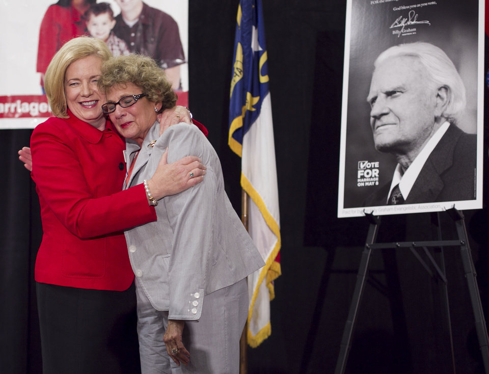 Photo -   Mary Frances Forrester, the wife of the late N.C. State Sen. James Forrester, right, embraces Tami Fitzgerald from Vote For Marriage NC as they celebrate the passage of Amendment One during an election night party Tuesday May 8, 2012 in Raleigh, N.C. Senator Forrester was the person who proposed Amendment One before his death. North Carolina voters approved the constitutional amendment Tuesday defining marriage solely as a union between a man and a woman, becoming the latest state to effectively slam the door shut on same-sex marriages. (AP Photo/The News & Observer, Robert Willett) MANDATORY CREDIT
