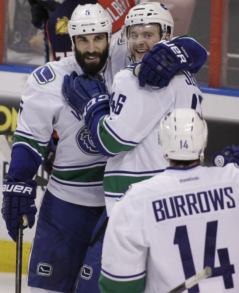Photo - Vancouver Canucks'  Nicklas Jensen, top right, of Denmark, celebrates with teammate Jason Garrison, left, and Alexandre Burrows (14) after scoring a goal during the first period of an NHL hockey game against the Florida Panthers, Sunday, March 16, 2014, in Sunrise, Fla. (AP Photo/Luis M. Alvarez)