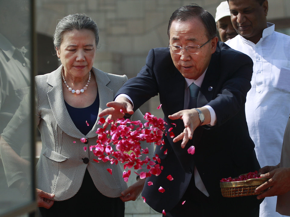 Photo -   U.N. Secretary-General Ban Ki-moon, right, throws flowers as wife Yoo Soon-taek looks on as they pay respects at Rajghat, the memorial to the late Mahatma Gandhi in New Delhi, India, Friday, April 27, 2012. Ban is on a three day official visit to India. (AP Photo/Kevin Frayer)