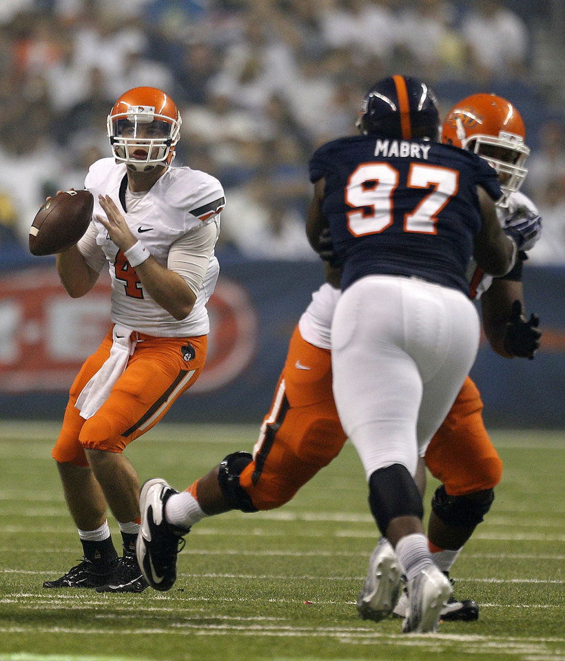 Photo - Oklahoma State's J.W. Walsh (4) looks to throw a pass during the second half of a college football game between the University of Texas at San Antonio Roadrunners (UTSA) and the Oklahoma State University Cowboys (OSU) at the Alamodome in San Antonio, Saturday, Sept. 7, 2013.  Photo by Sarah Phipps, The Oklahoman