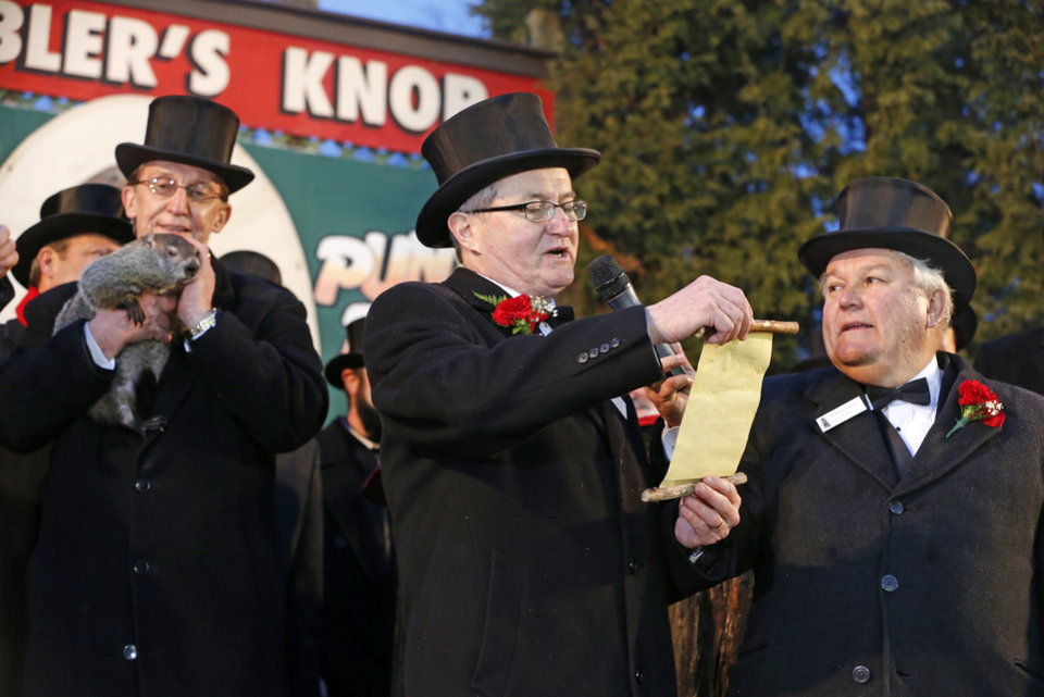 Photo - Punxsutawney Phil is held by Ron Ploucha, left, as Ground Club Vice President Jeff Lundy, center, reads the weather proclamation after Phil saw his shadow and predicted six more weeks of winter weather after, as Ground Club President, Bill Deeley, right, listens on Gobblers Knob in Punxsutawney, Pa.,  Sunday, Feb. 2, 2014.  (AP Photo/Gene J. Puskar)