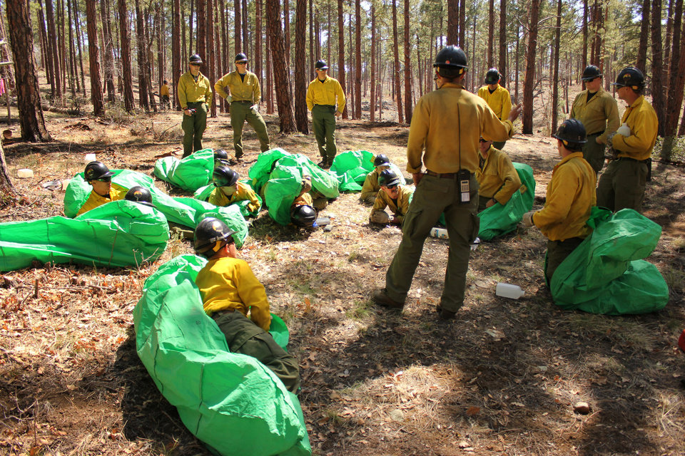 Photo - In this April 12, 2012 photo provided by the Cronkite News, Phillip Maldonado, a squad leader with the Granite Mountain Hotshots, trains crew members on setting up emergency fire shelters outside of Prescott, Ariz. On Sunday, June 30, 2013, 19 members of the Prescott-based crew were killed in the deadliest wildfire involving firefighters in the U.S. for at least 30 years. The firefighters were forced to deploy their emergency fire shelters - tent-like structures meant to shield firefighters from flames and heat - when they were caught near the central Arizona town of Yarnell, according to a state forestry spokesman. (AP Photo/Cronkite News, Connor Radnovich)