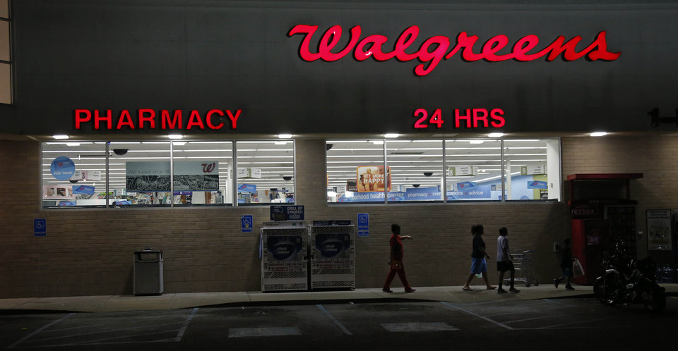 Photo - In this June 21, 2013 photograph, customers are seen leaving a Walgreens pharmacy in Jackson, Miss. Walgreen Co. reports quarterly financial results, Tuesday, June 25, 2013. (AP Photo/Rogelio V. Solis)