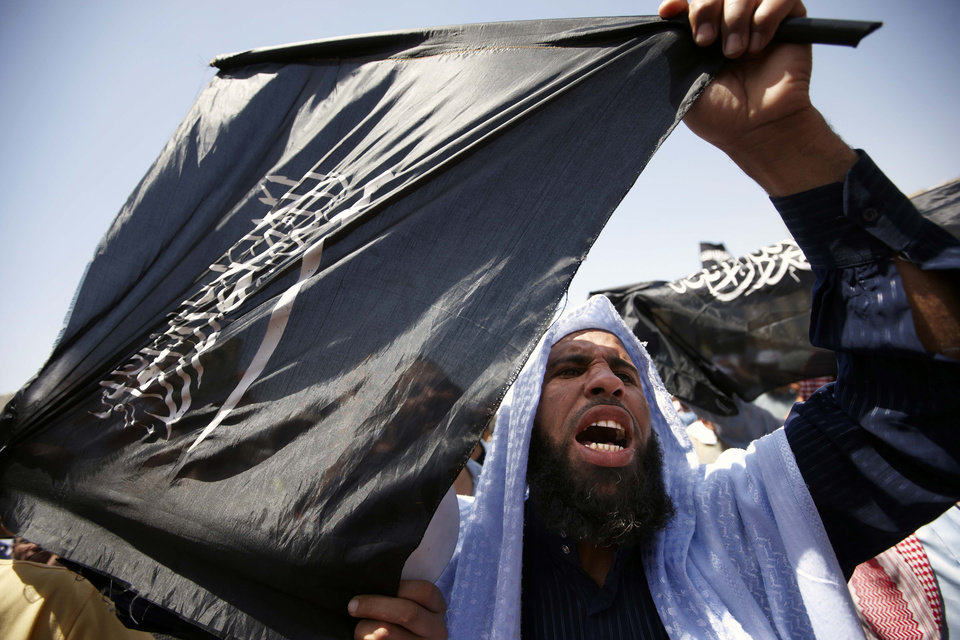 "FILE - In this Saturday, April 21, 2012 file photo, a follower of Egyptian Muslim cleric and former candidate for the presidency Hazem Abu Ismail holds an Islamist flag that reads, ""no god but Allah, Muhammad is the Prophet,"" during a demonstration in Tahrir Square, Cairo, Egypt. Internal divisions are threatening to unravel Egypt's second biggest political party, the political arm of the ultraconservative Salafis, the country's most hardline Islamist movement. Now its leaders are split over whether Muslim clerics or more pragmatic politicians should be steering the movement. (AP Photo/Fredrik Persson, File)"