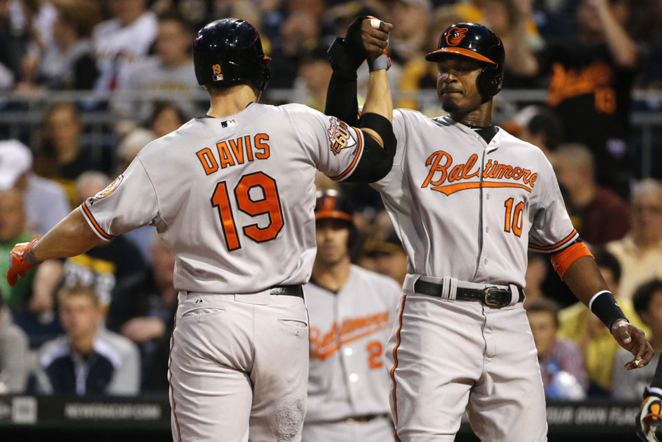 Photo - Baltimore Orioles' Chris Davis (19) is greeted by Adam Jones (10) who was on base for Davis' two-run home run off Pittsburgh Pirates starting pitcher Francisco Liriano during the fifth inning of a baseball game in Pittsburgh on Tuesday, May 20, 2014. (AP Photo/Gene J. Puskar)