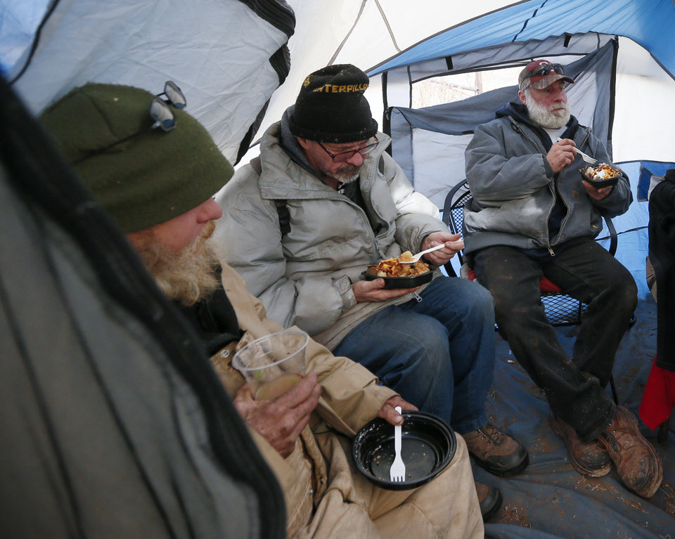"Photo - From left, Tim, 57, nicknamed ""Old Man"" and who preferred not to give his last name, Luther, 52, who preferred not to give his last name, and Eli Hail, 40, eat lunch inside of a tent at 6100 S Cox, near the original location of Joe's Addiction, in Valley Brook, Okla., Monday, Dec. 23, 2019. While the new site for Joe's Addiction is not ready, Jamie Zumwalt, not pictured, and others continue to help the community of people in need who were being served by Joe's Addiction. [Nate Billings/The Oklahoman]"