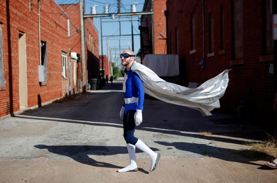 Photo -  Tom Kenworthy from Tulsa, dressed as Cerulian Bolt, walks the streets of downtown Pauls Valley during International Superhero Day, Saturday, August 4, 2012.