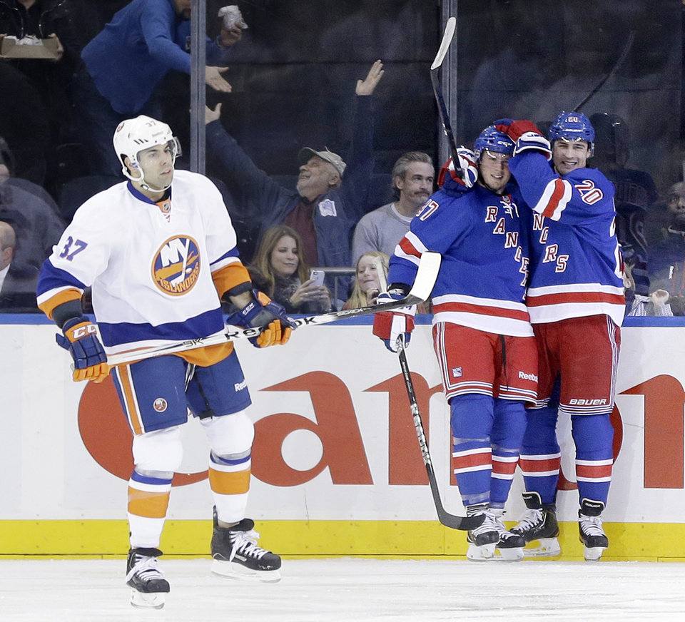 New York Rangers' Chris Kreider, right, celebrates after teammate J.T. Miller, center, scored a goal while New York Islanders' Brian Strait skates past during the first period of the NHL hockey game in New York, Thursday, Feb. 7, 2013.  (AP Photo/Seth Wenig)