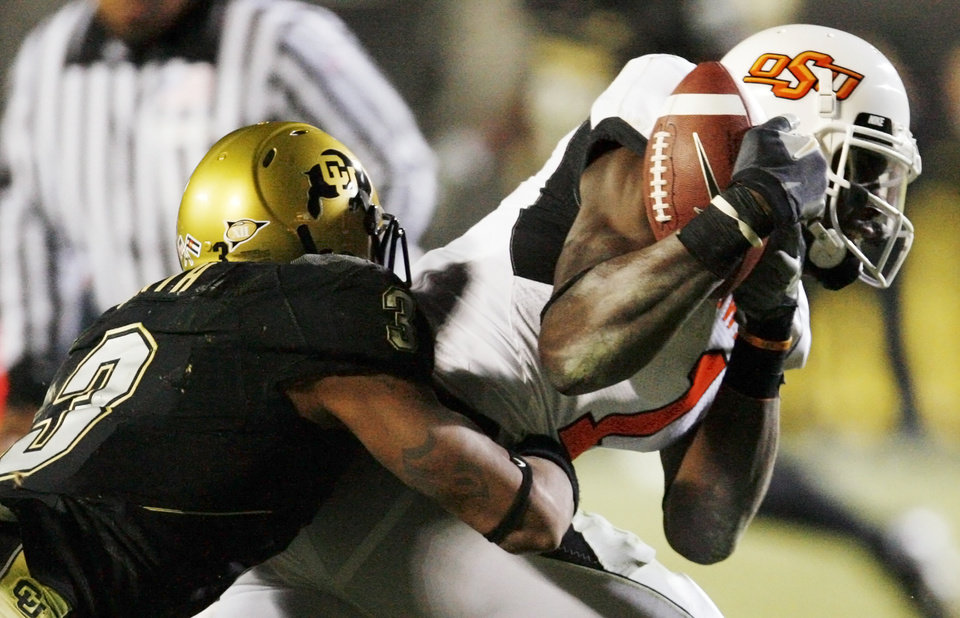 Photo - OSU's Dez Bryant (1) makes a catch and is tackled by Jimmy Smith (3) of Colorado in the third quarter during the college football game between Oklahoma State University and University of Colorado at Folsom Field in Boulder, Colo., Saturday, Nov. 15, 2008. OSU won, 30-17. BY NATE BILLINGS, THE OKLAHOMAN
