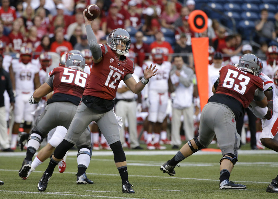 Photo - Washington State quarterback Connor Halliday passes against Rutgers in the first half of an NCAA college football game, Thursday, Aug. 28, 2014, in Seattle. (AP Photo/Ted S. Warren)