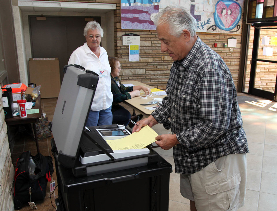 Photo - Don Lomangino inserts his ballot at the John Knox Church precinct for the runoff election as precinct worker Talca Harris watches in Tulsa, Okla., Tuesday, Aug. 28, 2012. (AP Photo/Tulsa World, Stephen Pingry) ORG XMIT: OKTUL101