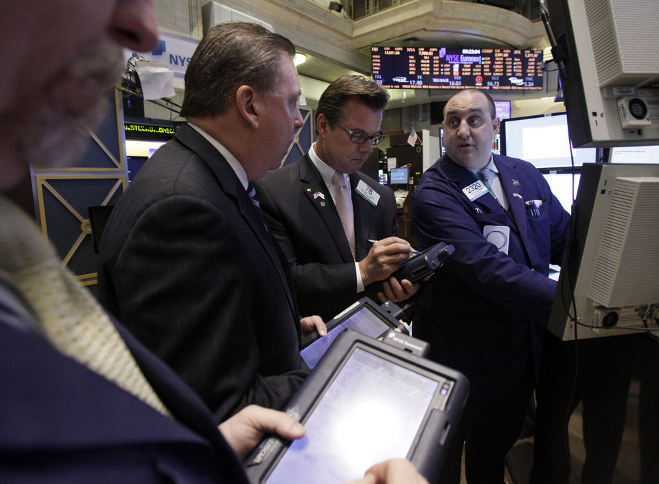 Photo - Specialist Peter Giacchi, right, works on the floor of the New York Stock Exchange Wednesday, April 25, 2012. Apple's stock shot up more than $50 a share Wednesday after its quarterly profit blew away Wall Street expectations. (AP Photo/Richard Drew) ORG XMIT: NYRD106
