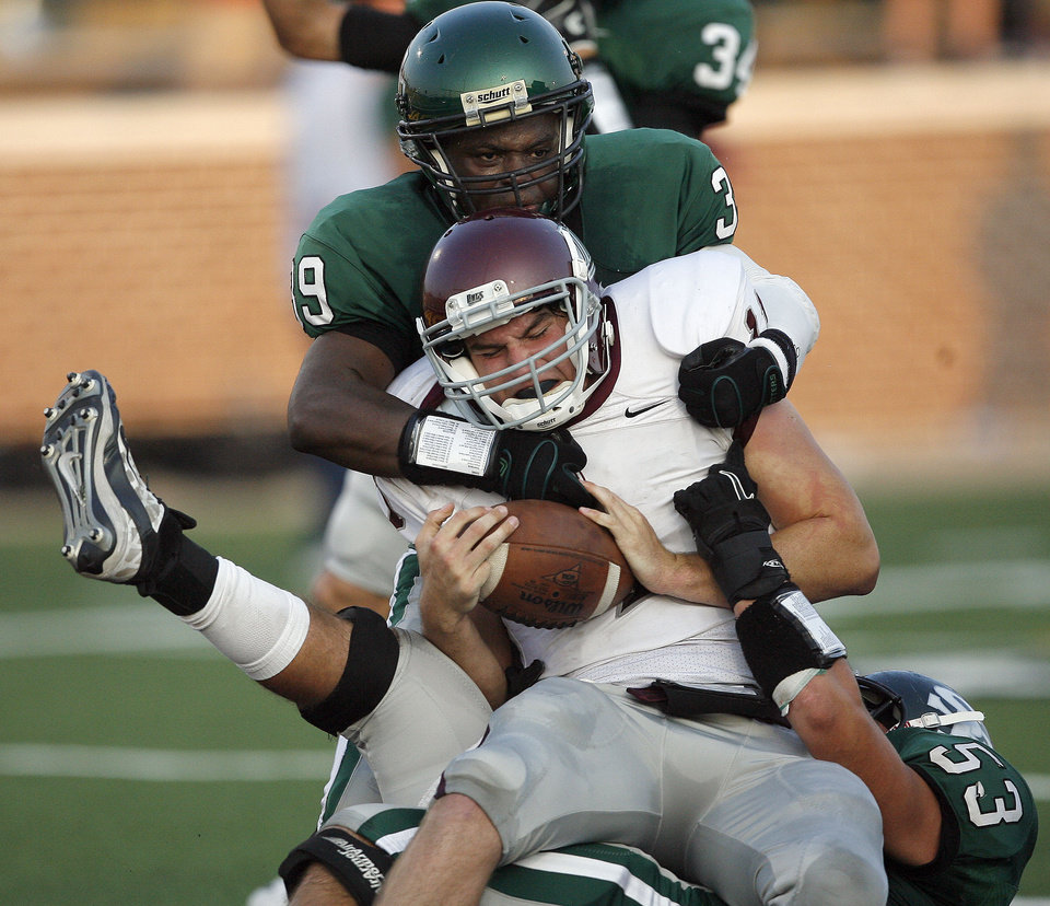 Edmond Santa Fe's Carlos Washington, top, and Josh Crouch sack Edmond Memorial's Ry Huff for a safety during the high school football game between Edmond Santa Fe and Edmond Memorial at Wantland Stadium in Edmond, Okla.,  Friday, Sept. 2, 2011. Photo by Sarah Phipps, The Oklahoman