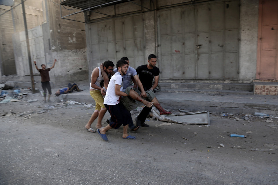 Photo - Palestinians rush an injured man following an Israeli Strike in Shijaiyah neighborhood, eastern Gaza City, Wednesday, July 30, 2014. (AP Photo/Adel Hana)