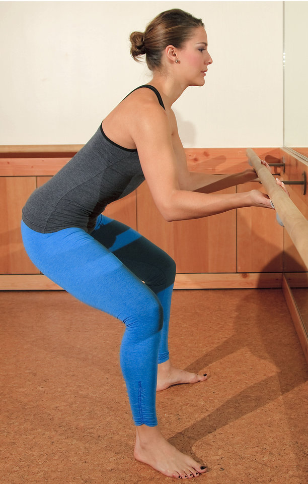 Photo - Model Emoly demonstrates Sumo, a Barre3 posture. Underhand grip the barre, bend your knees over your ankles and hinge forward at the waist. Spine is elongated reaching the behind you. Targets the hamstrings and inner thighs. Photo by Chris Landsberger, The Oklahoman.  CHRIS LANDSBERGER