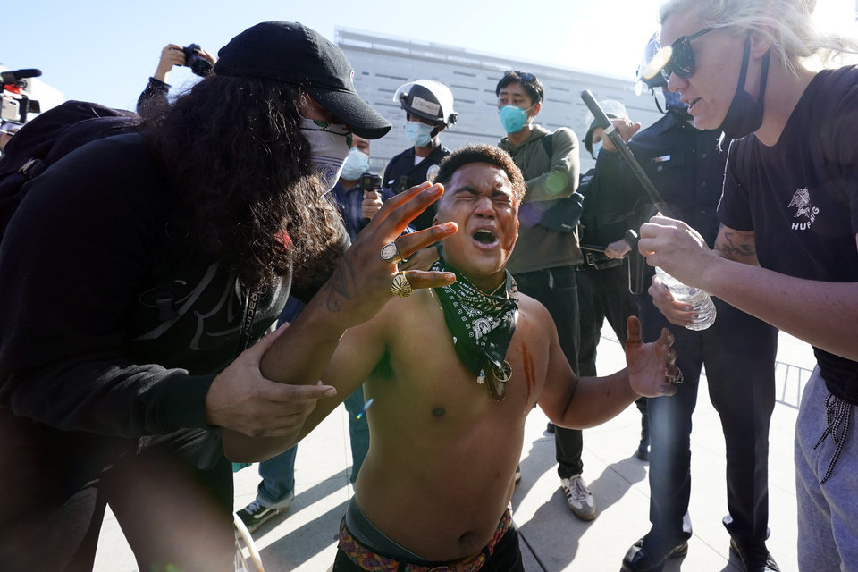 Photo - A counter demonstrator, center, yells after getting maced in the face by far-right demonstrators outside of City Hall Wednesday, Jan. 6, 2021, in Los Angeles. Demonstrators supporting President Donald Trump are gathering in various parts of Southern California as Congress debates to affirm President-elect Joe Biden's electoral college victory. (AP Photo/Marcio Jose Sanchez)