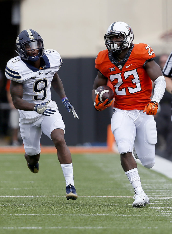 Photo - Oklahoma State running back Rennie Childs, right, rushes for a touchdown as Pittsburgh's Jordan Whitehead tries to chase him down on Saturday at Boone Pickens Stadium. (Photo by Sarah Phipps, The Oklahoman)