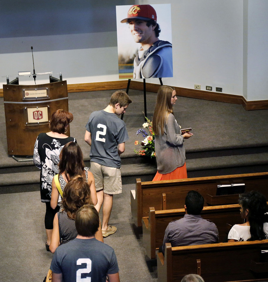Photo - People file past a large portrait showing Christopher Lane in his East Central University baseball uniform as they take their seats in a front pew before a memorial service begins Saturday, Aug.24, 2013. Lane, a 22-year-old Australian collegiate baseball player, was shot in the back and killed last week as he was jogging in an affluent neighborhood in Duncan, in south-central Oklahoma. (AP Photo/The Oklahoman, Jim Beckel) LOCAL STATIONS OUT (KFOR, KOCO, KWTV, KOKH, KAUT OUT); LOCAL WEBSITES OUT; LOCAL PRINT OUT (EDMOND SUN OUT, OKLAHOMA GAZETTE OUT) TABLOIDS OUT ORG XMIT: OKOKL103