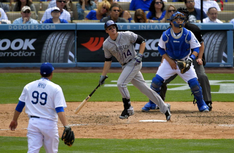 Photo - Colorado Rockies' Josh Rutledge, center, hits a three-run home run as Los Angeles Dodgers starting pitcher Ryu Hyun-Jin, left, of South Korea, and catcher Tim Federowicz look on during the sixth inning of a baseball game, Sunday, April 27, 2014, in Los Angeles. (AP Photo/Mark J. Terrill)