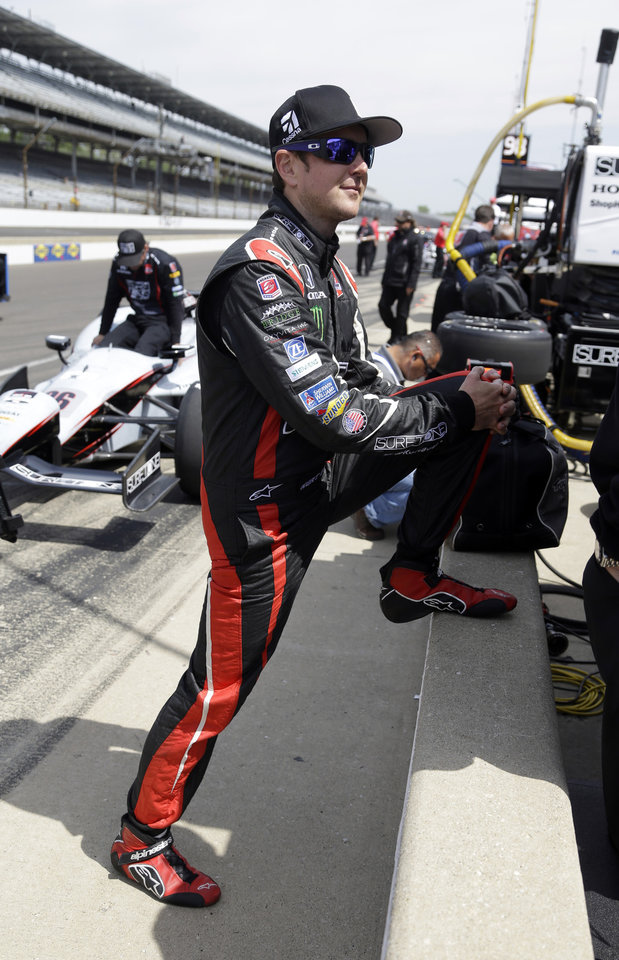 Photo - In this May 19, 2014 photo, Kurt Busch stretches before the star of practice for the Indianapolis 500 IndyCar auto race at the Indianapolis Motor Speedway in Indianapolis. Busch will attempt to drive both the Indianapolis 500 and the NASCAR Coca-Cola 600 in Charlotte, NC. on Sunday.  (AP Photo/Michael Conroy)
