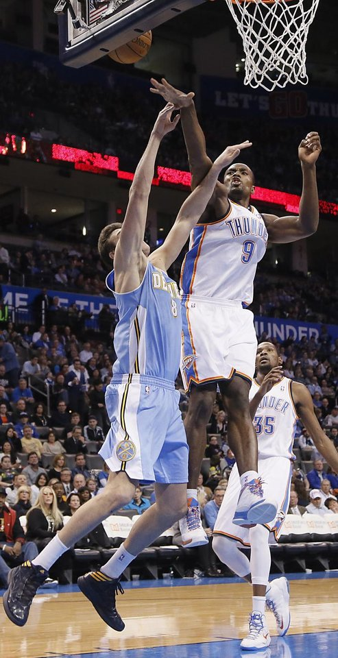 Photo - Oklahoma City's Serge Ibaka (9) blocks a shot by Denver's Danilo Gallinari (8) during the NBA basketball game between the Oklahoma City Thunder and the Denver Nuggets at the Chesapeake Energy Arena on Wednesday, Jan. 16, 2013, in Oklahoma City, Okla.  Photo by Chris Landsberger, The Oklahoman