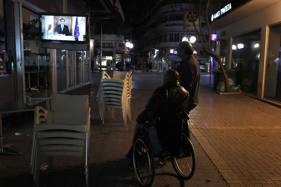 Photo - Cypriots watch a TV screen as President of Cyprus Nicos Anastasiades addresses to the nation in capital Nicosia, Monday, March 25, 2013. Anastaciates said that the central bank will impose some limits on bank transactions on Tuesday, when most of the country's financial institutions reopen for the first time in over a week. (AP Photo/Petros Giannakouris)