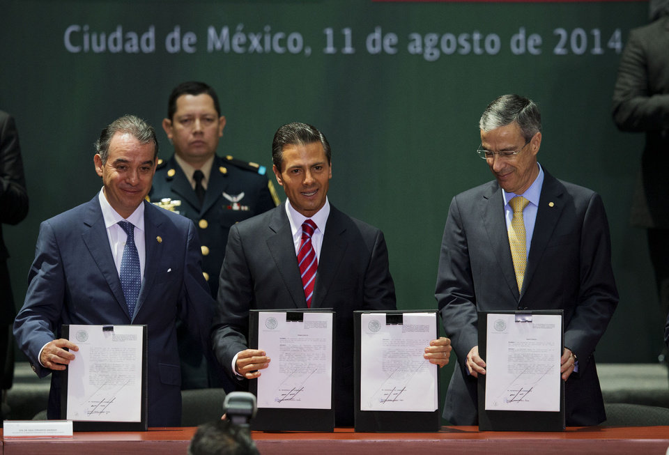 Photo - Mexican President Enrique Pena Nieto, center, Senate leader Raul Cervantes Andrade, left, and House Speaker Jose Gonzalez Morfin hold up signed documents at a ceremony to mark the signing of a historic energy reform bill, at the National Palace in Mexico City, Monday, Aug. 11, 2014. The law will open the state-run oil, gas and electricity industries to foreign and private companies. Mexico is hoping for tens of billions of dollars in outside investment in deep-water oil drilling and shale gas production. (AP Photo/Rebecca Blackwell)
