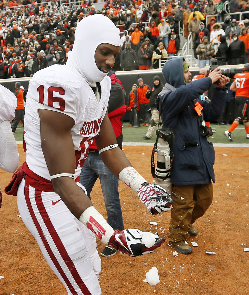 Photo - Oklahoma's Jaz Reynolds (16) catches a snowball thrown onto the field from the OSU student section after the Bedlam college football game between the Oklahoma State University Cowboys (OSU) and the University of Oklahoma Sooners (OU) at Boone Pickens Stadium in Stillwater, Okla., Saturday, Dec. 7, 2013. OU won, 33-24. Photo by Nate Billings, The Oklahoman