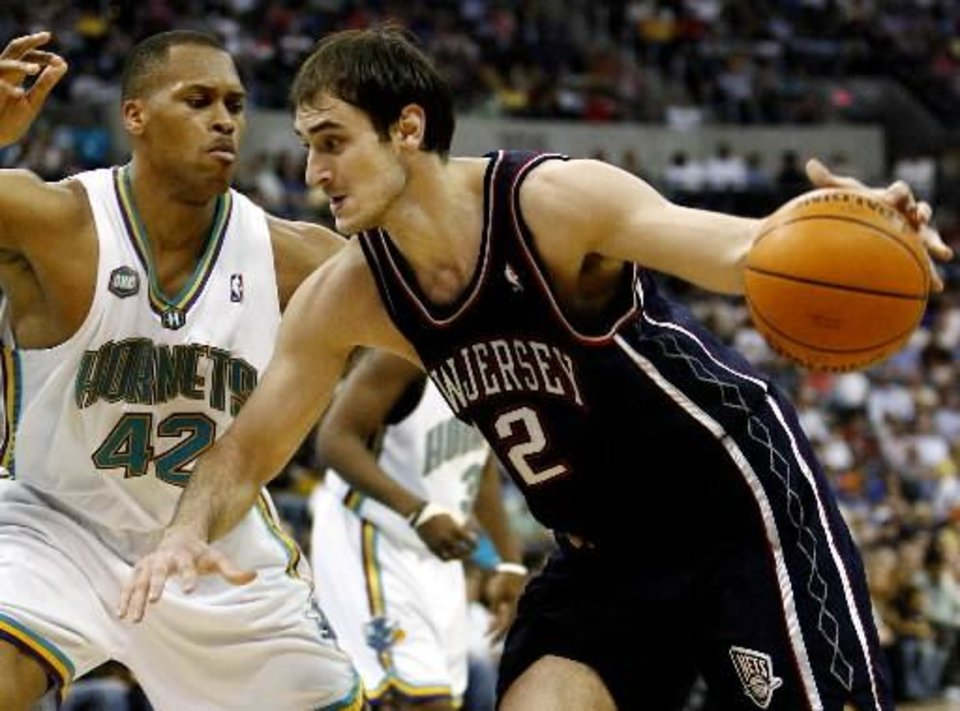 New Jersey Nets center  Nenad  Krstic (12) of Serbia drives the ball past New Orleans/Oklahoma City Hornets center PJ Brown (42) in the first half of an NBA basketball game Sunday, March. 12, 2006, in Oklahoma City. (AP Photo/Ty Russell)