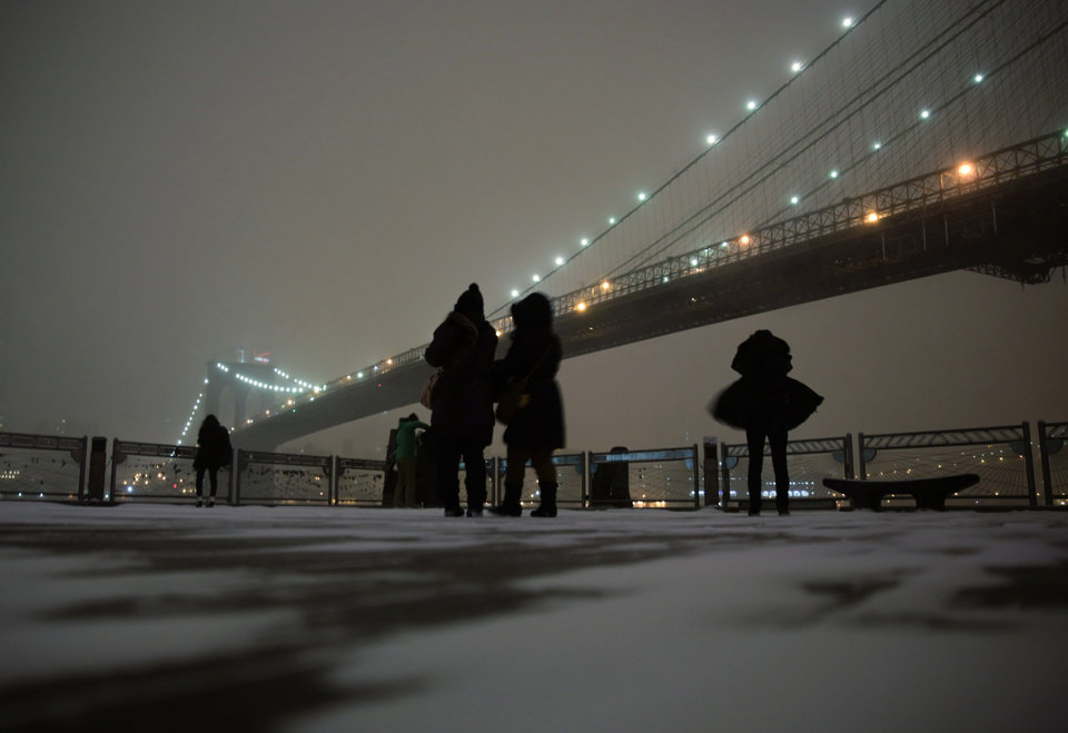 Photo - Visitors stop on the waterfront in Brooklyn to photograph the Brooklyn Bridge during a winter storm in New York, Thursday, Jan. 2, 2014. The storm is expected to bring snow, stiff winds and punishing cold into the Northeast. (AP Photo/Peter Morgan)
