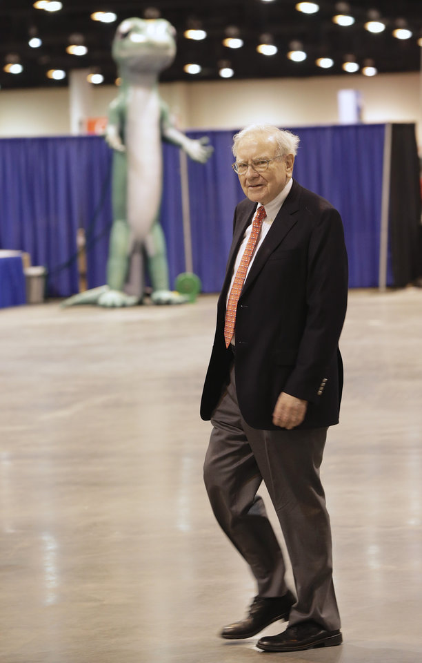 Photo - Billionaire investor Warren Buffett walks past the Geico gecko Friday, May 2, 2014, in Omaha, Neb., as he tours the exhibitor's floor where Berkshire Hathaway subsidiaries display their wares to thousands of Berkshire Hathaway shareholders who are in town for the annual shareholders meeting which takes place on Saturday. (AP Photo/Nati Harnik)