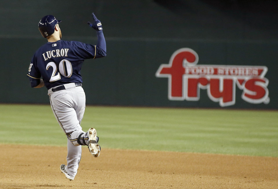 Photo - Milwaukee Brewers' Jonathan Lucroy raises his arm in celebration as he rounds the bases after hitting a grand slam against the Arizona Diamondbacks during the seventh inning of a baseball game on Tuesday, June 17, 2014, in Phoenix. (AP Photo/Ross D. Franklin)